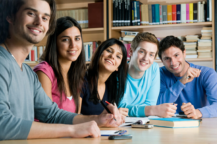 Happy group of young students studying together in a college lib